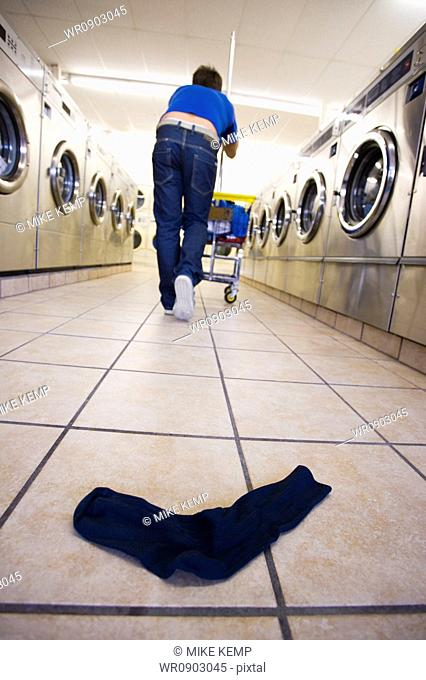 One sock on floor at Laundromat with man and trolley