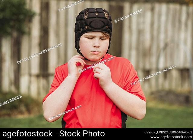 Boy putting on rugby protection head gear in backyard