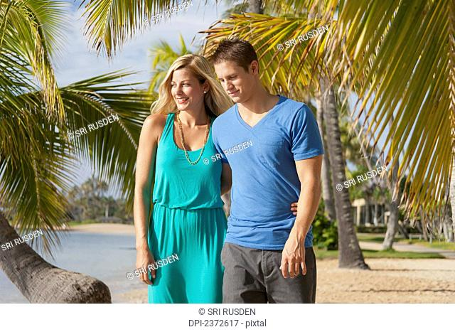 A couple walk on a beach with palm trees along the water's edge; Honolulu, Hawaii, United States of America