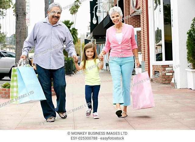 Senior Couple With Granddaughter Carrying Shopping Bags