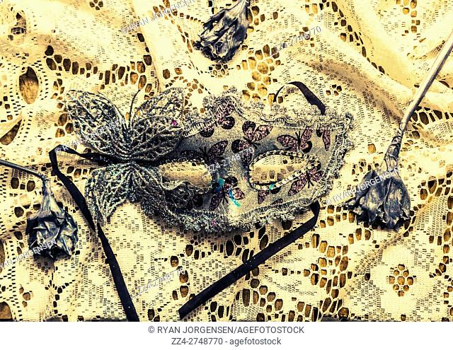 Silver masquerade mask on classy lace fabric beside wilted dead flowers. Dead blossoms days