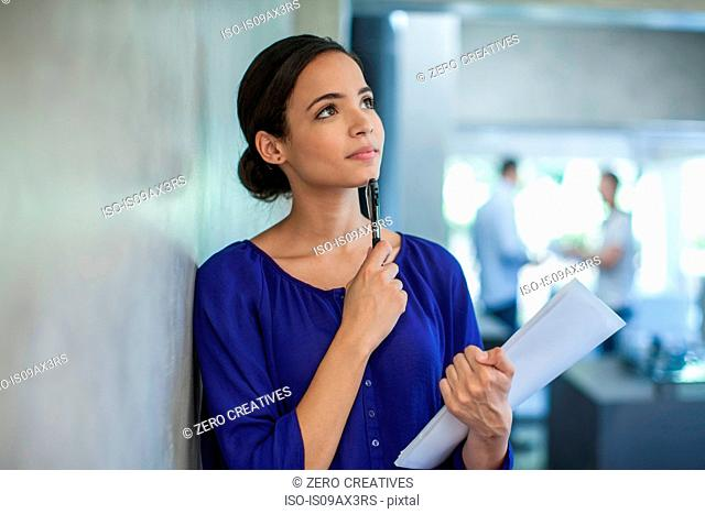 Young female designer leaning against wall thinking in design office