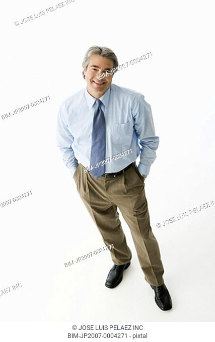 Hispanic man standing with hands in pockets