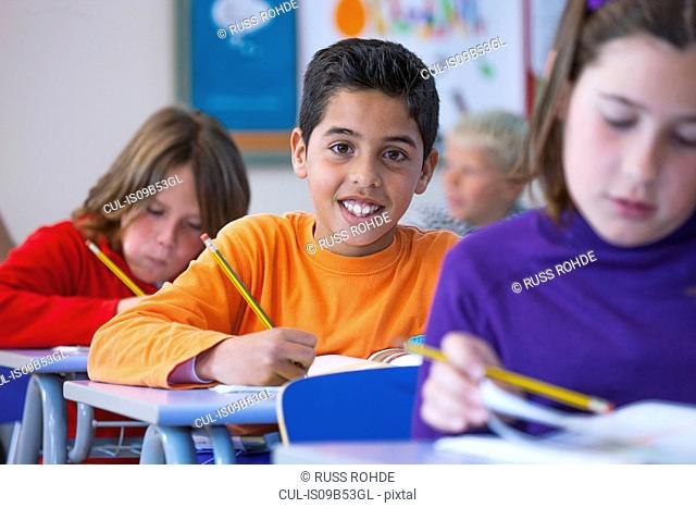 Portrait of boy in classroom, sitting at desk, doing classwork