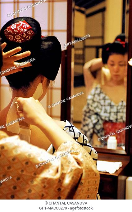 A MAIKO APPRENTICE GEISHA WITH HER TRADITIONAL MAKEUP DORAN. APPLICATION OF A WHITE FOUNDATION SHIRONURI ON HER NECK WITH A BAMBOO BRUSH BURASHI