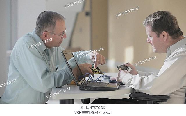 Two Electronics Design Engineers reviewing final design of circuit board, one man quadriplegic in a wheelchair