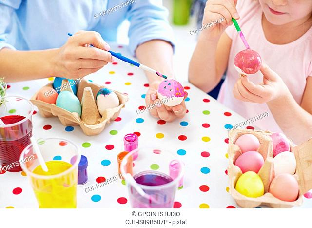 Cropped shot of woman and daughter's hands painting easter eggs at table