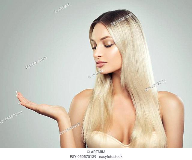 Pretty Woman with Natural Makeup, Fresh Skin and Blonde Hair Showing Empty Copy Space on the Open Hand on White Background