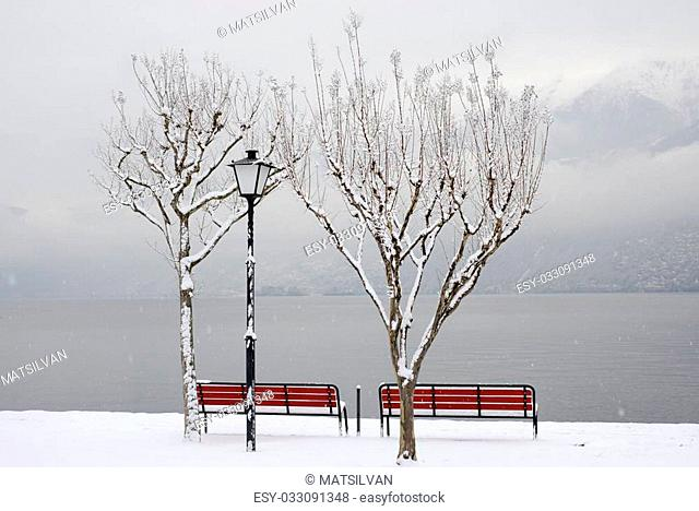 Bench on lakefront when it's snowing in winter with mountain