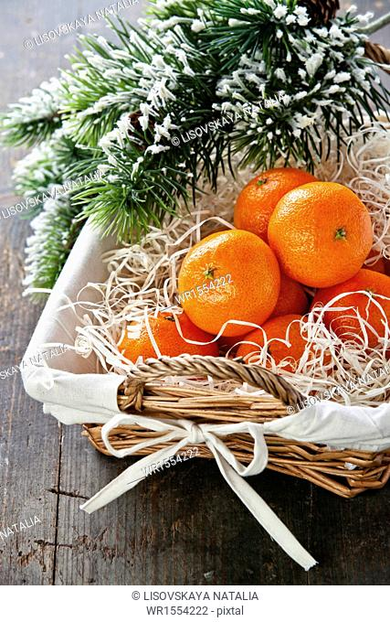Mandarins in basket with Christmas tree branch