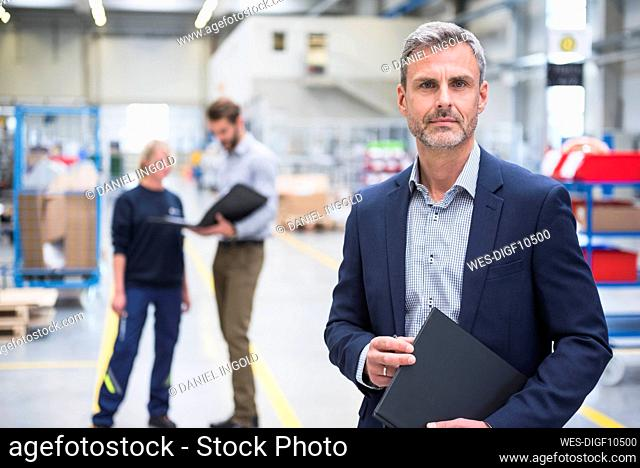 Portrait of a confident mature businessman in a factory with colleagues in background