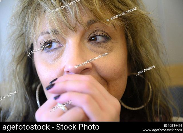 51 year old blond woman hands on chin, looking away from the camera