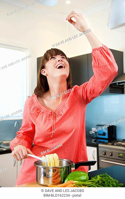 Caucasian woman testing pasta and cooking in kitchen