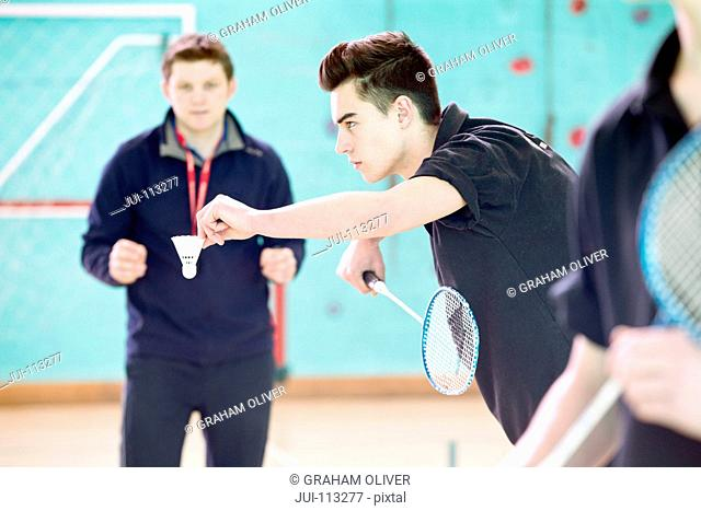 Focused high school student playing badminton in gym class