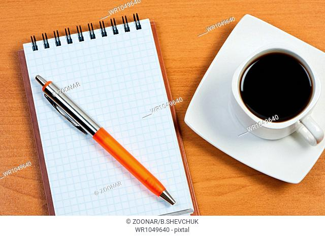 Notebook with pen and coffee on table top view