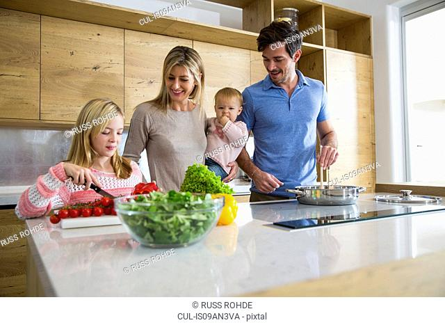 Girl and family preparing fresh vegetables in kitchen