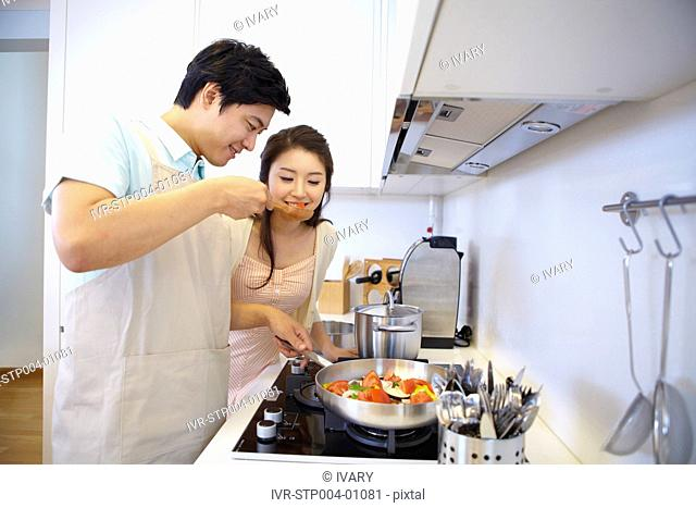 Couple Cooking Food In Kitchen