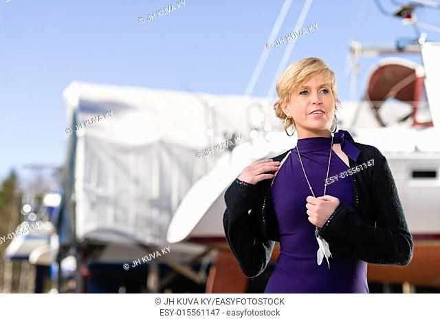 Mature woman wearing purple dress and posing, sailboat on background