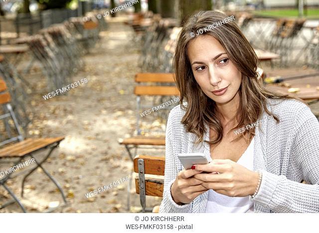Portrait of pensive woman with smartphone in autumnal beer garden