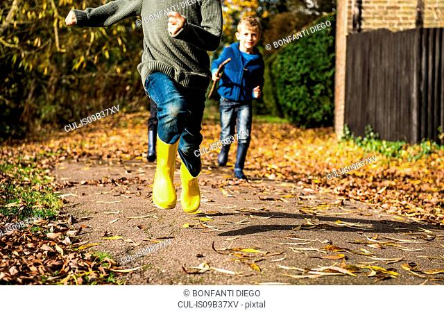 Three boys, running along pathway in autumn, low section