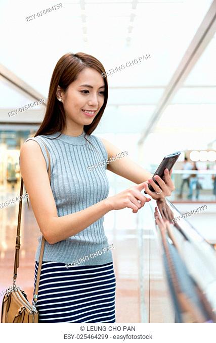Asian woman using the cellphone for upload the status at shopping mall