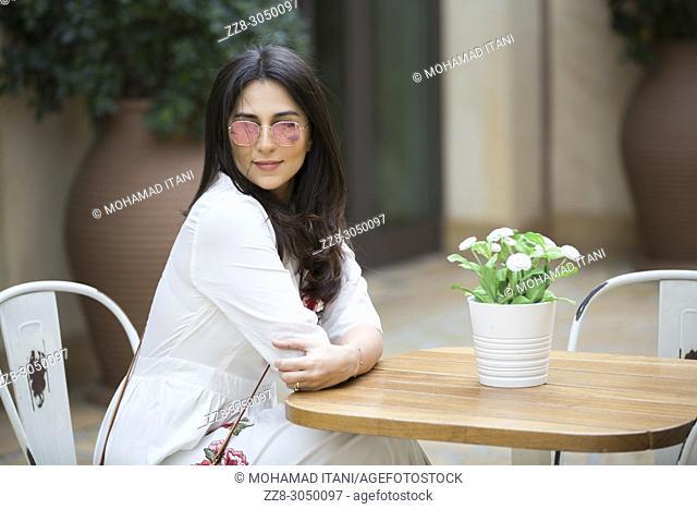 Beautiful woman wearing sunglasses sat in a cafe at Madinat Jumeirah souk Dubai UAE