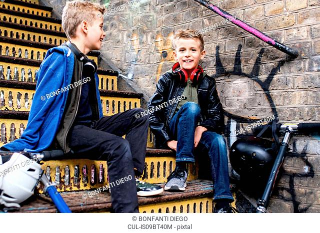 Twins talking on metal staircase