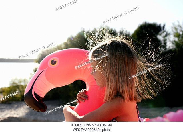 Girl hugging flamingo pool float