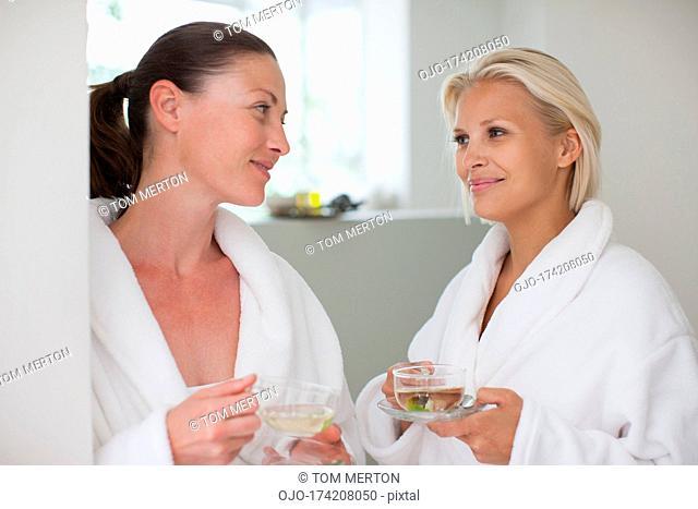 Friends in bathrobes drinking tea at spa