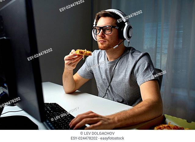 technology, gaming, entertainment, let's play and people concept - young man in headset with pc computer eating pizza while playing game at home and...