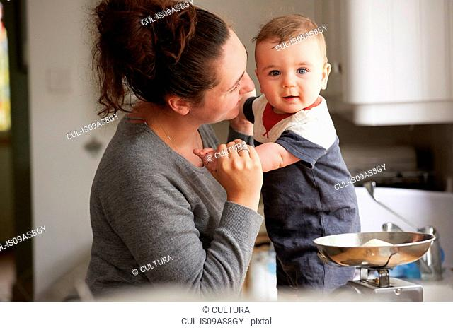 Mother holding baby boy on kitchen counter