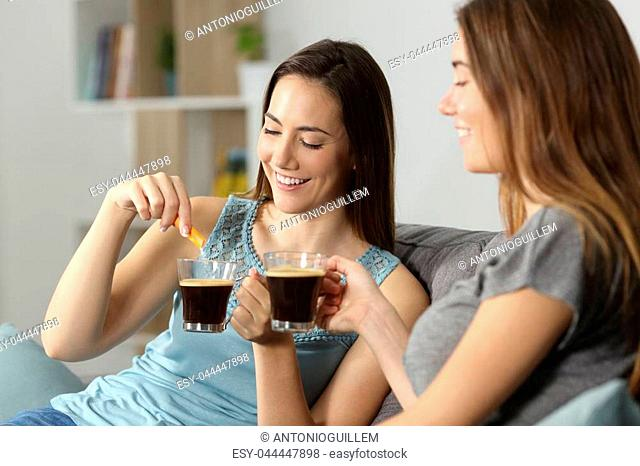 Women drinking coffee throwing sugar into cup sitting on a couch in the living room at home