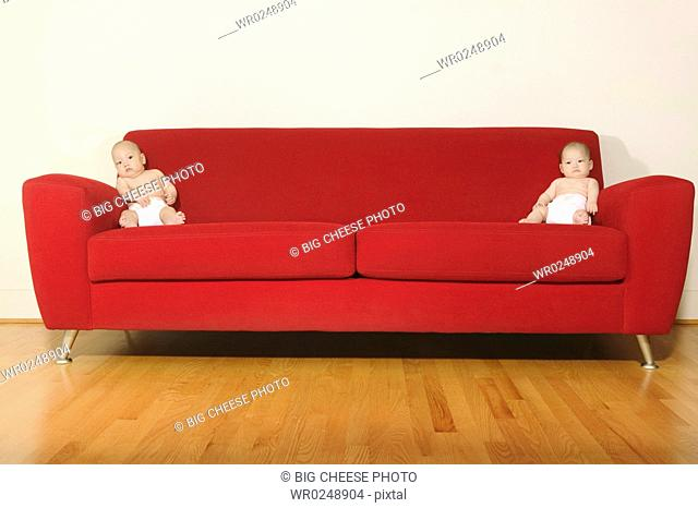 Twin babies on each end of a red sofa