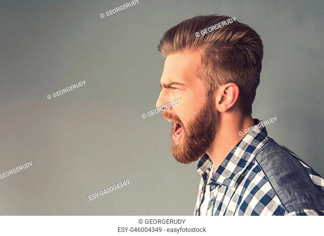 Side view of handsome bearded man in casual clothes screaming, on gray background