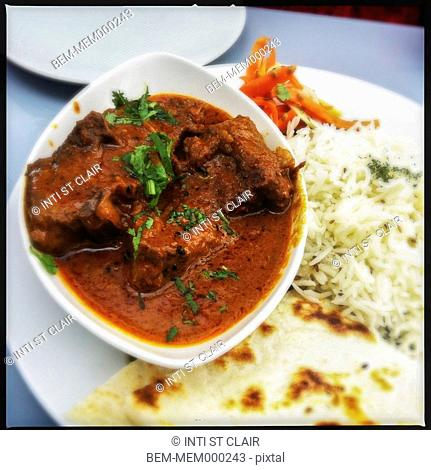 Meat in sauce, rice and bread on plate