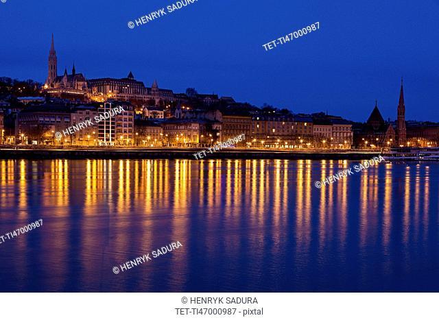 Illuminated skyline reflecting in Danube River