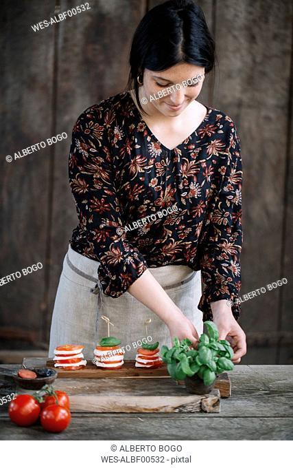 Woman preparing Caprese Salad