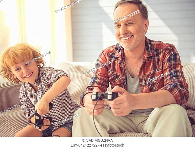 Handsome grandpa and grandson are playing game console and smiling while spending time together at home