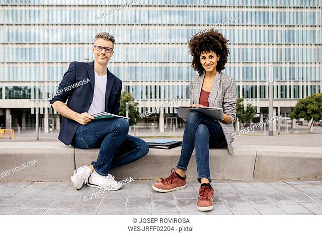 Portrait of two confident colleagues working together outside office building