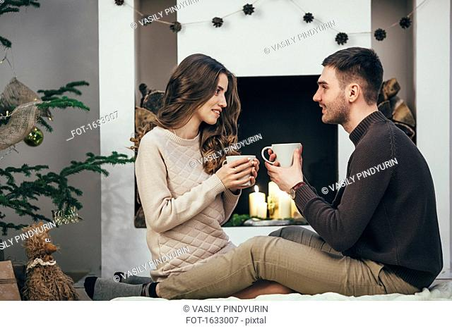 Smiling couple having coffee while sitting on rug at home during Christmas