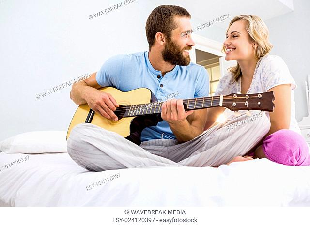 Man and woman playing guitar in bed