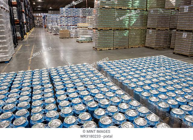 Cans of flavoured water stored in the warehouse of a large bottling plant
