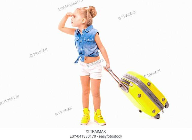 Isolated on white, cute little caucasian blonde girl in blue shirt, white shorts, sunglasses and yellow boots hold yellow suitcase by the handle, hand on head