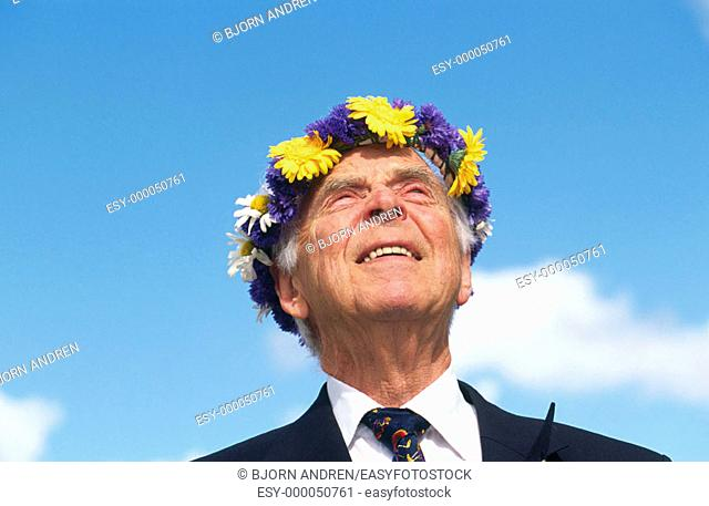 Elderly man with wreath of flowers