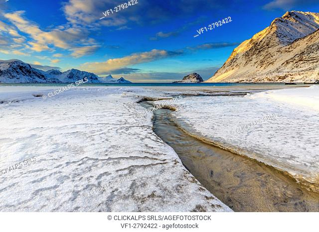The golden sunrise reflected in a clear stream of the sea where the snow has melted. Haukland Lofoten Islands Norway Europe