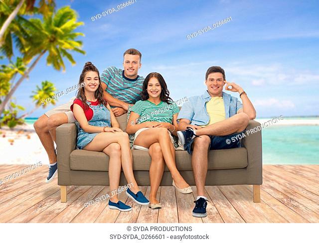 friends sitting on sofa over tropical beach