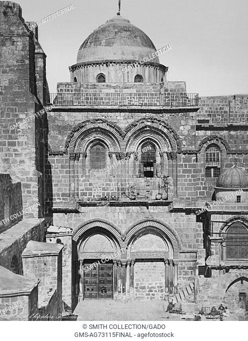 A photograph of the entrance to the Church of the Holy Sepulchre, the building is a stone work structure that has doorways and windows accented by stone...