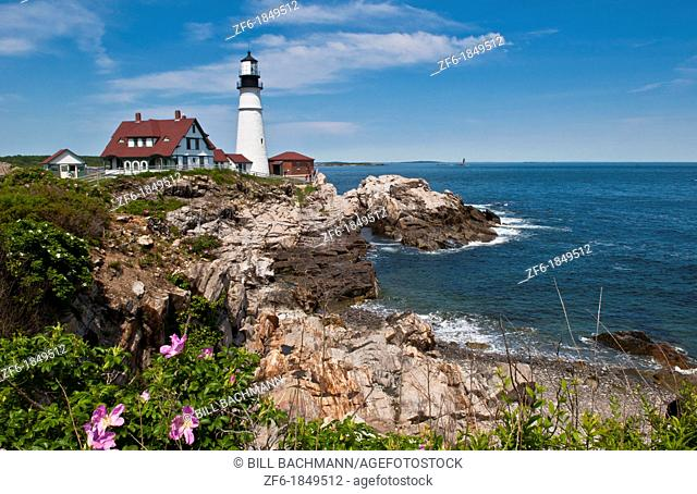Beautiful scenic Maine in Portland Maine at the Portland Head Lighthouse with rocks on shore and flowers
