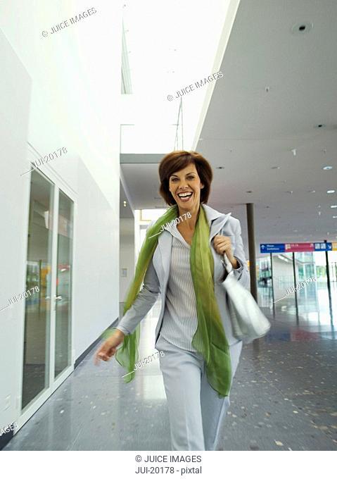 Energetic woman walking in corridor