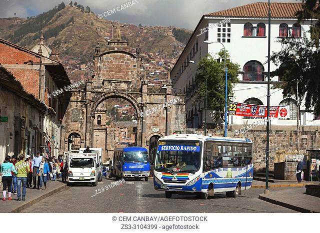 View to the Arco Santa Clara- Santa Clara Arch with local buses in the foreground at the historic center, Cusco, Peru, South America